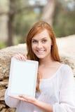 Mujer que exhibe una pantalla en blanco de la tableta Imagen de archivo libre de regalías