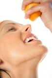 Mujer que exprime la naranja en boca Imágenes de archivo libres de regalías