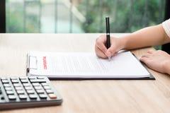 Mujer que firma en contrato confidencial con la calculadora en de madera foto de archivo libre de regalías