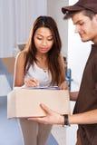 Mujer que firma mientras que recibe el mensajero Foto de archivo libre de regalías