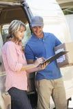 Mujer que firma para el embalador entregado por el mensajero Imagen de archivo