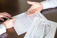 Mujer que firma un contrato de las propiedades inmobiliarias Imágenes de archivo libres de regalías