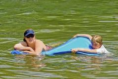Mujer que flota en agua foto de archivo