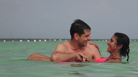 Mujer que flota en agua con el hombre almacen de metraje de vídeo