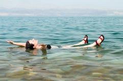 Mujer que flota en agua del mar muerto Imágenes de archivo libres de regalías