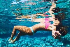 Mujer que flota en agua tropical Imágenes de archivo libres de regalías