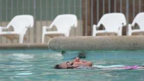 Mujer que flota en piscina almacen de metraje de vídeo