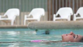 Mujer que flota en piscina almacen de video
