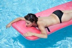 Mujer que flota en piscina con la tapa apagado Imagenes de archivo