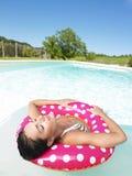 Mujer que flota en piscina con los ojos cerrados Foto de archivo