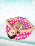 Mujer que flota en piscina con los ojos cerrados Fotos de archivo libres de regalías