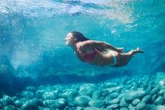 Mujer que flota en piscina natural foto de archivo libre de regalías