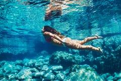 Mujer que flota en piscina natural foto de archivo