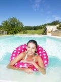 Mujer que flota en piscina y que disfruta de la bebida Imagenes de archivo
