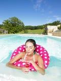 Mujer que flota en piscina y que disfruta de la bebida Imagen de archivo libre de regalías