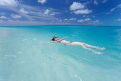 Mujer que flota en una parte posterior en el mar hermoso imagenes de archivo