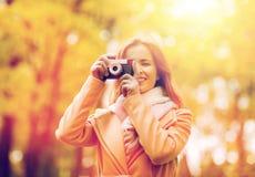 Mujer que fotografía con la cámara en parque del otoño Imagen de archivo libre de regalías