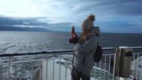 Mujer que fotografía el mar congelado de la nave