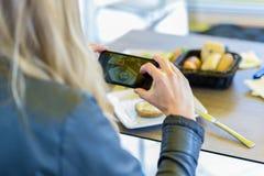 Mujer que fotografía la comida con el teléfono móvil Imagen de archivo