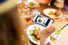 Mujer que fotografía la comida por smartphone Fotografía de archivo libre de regalías