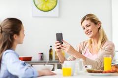 Mujer que fotografía a la hija por smartphone en casa Foto de archivo libre de regalías