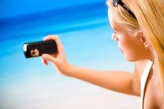 Mujer que fotografía por el teléfono celular Imagen de archivo libre de regalías