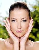 Mujer que frota ligeramente su piel limpia fresca de la cara imagenes de archivo