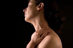 Mujer que frota suavemente su cuello fotografía de archivo