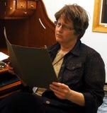 Mujer que frunce el ceño que mira los papeles en carpeta Imagen de archivo libre de regalías