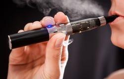 Mujer que fuma con el cigarrillo electrónico Imágenes de archivo libres de regalías