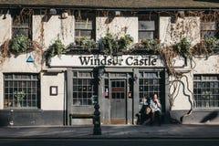 Mujer que fuma fuera del pub de Windsor Castle en Holland Park, Londres, Reino Unido foto de archivo