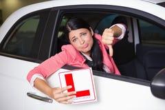 Mujer que gesticula los pulgares hacia abajo que sujetan una muestra del conductor del principiante Fotografía de archivo libre de regalías
