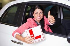 Mujer que gesticula los pulgares que muestran una muestra del conductor del principiante Fotografía de archivo libre de regalías