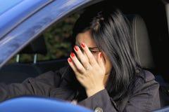 Mujer que golpea un coche que consigue en un accidente Foto de archivo libre de regalías