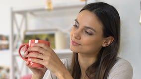 Mujer que goza de la bebida caliente en atmósfera casera, la relajación y la armonía acogedoras almacen de video