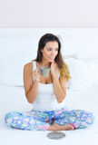 Mujer que goza de su café de la mañana en cama Imagen de archivo