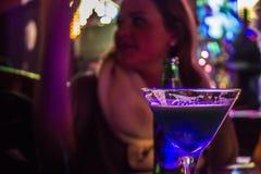 Mujer que goza de un cóctel en una barra Imagenes de archivo