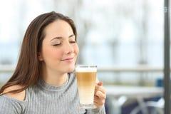 Mujer que goza de un café del macchiato Fotografía de archivo libre de regalías