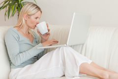 Mujer que goza de un sorbo de café mientras que trabaja en su computadora portátil Fotos de archivo