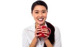 Mujer que goza del café durante rotura de trabajo Imagen de archivo
