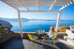Mujer que goza del desayuno con hermosa vista sobre Santorini fotos de archivo