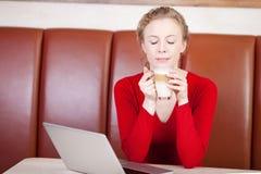 Mujer que goza del latte del caffee en café fotografía de archivo
