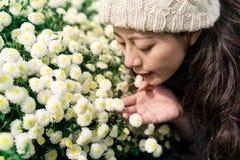 Mujer que goza del olor de flores en Tongluo imágenes de archivo libres de regalías