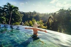 mujer que goza del sol en la piscina del verano del infinito en el centro turístico lujoso Imagen de archivo libre de regalías