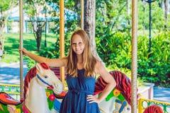 Mujer que goza en funfair y que monta en casa colorida del carrusel Imagenes de archivo