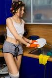 Mujer que goza lavando platos Fotos de archivo