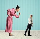 Mujer que grita en el pequeño hombre sorprendente Imagen de archivo