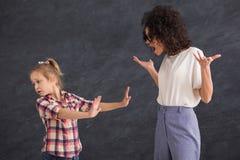 Mujer que grita en muchacha del niño en el fondo gris del estudio Foto de archivo