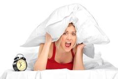 Mujer que grita y que cubre sus oídos con la almohadilla Imágenes de archivo libres de regalías