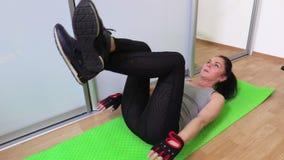 Mujer que guarda las piernas para arriba y que hace los ejercicios de la aptitud para los ABS almacen de video